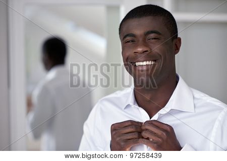 handsome professional african black man getting ready morning routine shirt at home for work