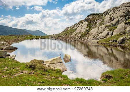 Small mountain lake in Retezat National Park, Transylvania, Romania, Europe. Blue sky with white clouds above.