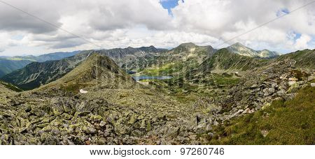 Extra high resolution detailed landscape panorama of Retezat National Park mountains in South Carpatians, Transylvania, Romania, Europe. Small lake with blue sky reflection at center.