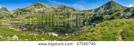 Extra high resolution detailed landscape panorama of Bucura lake in Retezat National Park mountains, South Carpatians, Transylvania, Romania, Europe. Small lake with blue sky reflection at center.