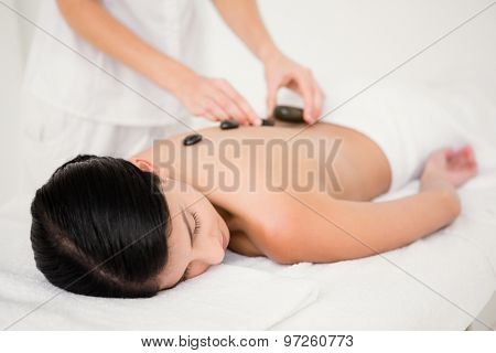 Pretty woman receiving a hot stone massage at the health spa