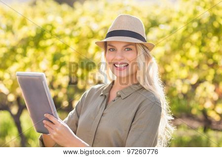 Portrait of a smiling blonde woman using a tablet