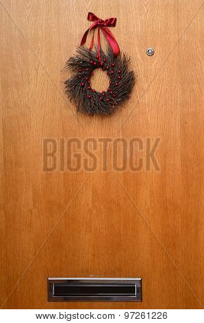 Wooden Door With A Christmas Wreath And Mailbox