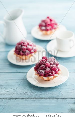 Raspberry tartlets with cream filling and dusted with icing sugar