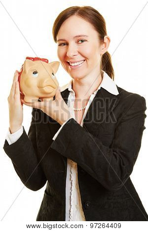 Happy business woman with a piggy bank as money investment