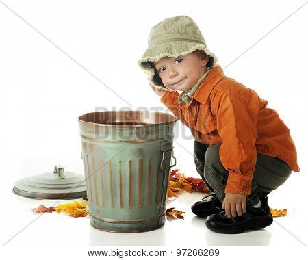 An adorable preschooler in fall colors squatting beside a small trash can as he cleans up fallen autumn leaves.  On a white background.