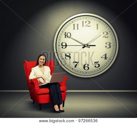 smiley woman with laptop sitting on the red chair over grey wall with big clock