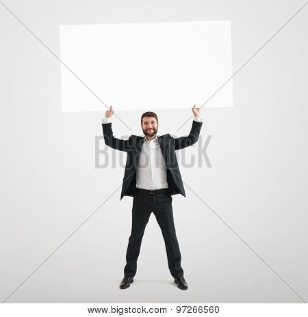 smiley businessman in formal wear holding empty banner and looking at camera over light grey background