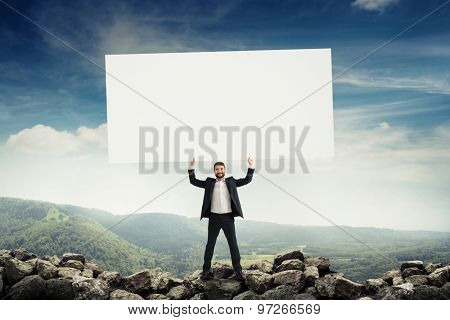 smiley businessman holding big empty placard over beautiful landscape with hills and forests
