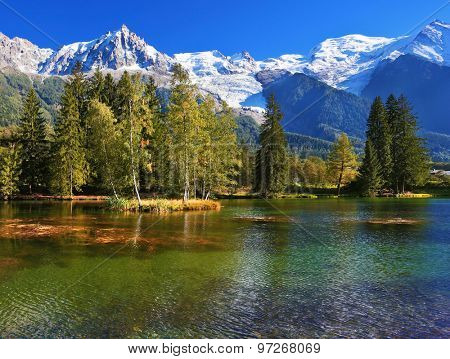 Lake with cold water surrounded by trees and snow-capped mountains. City park in the Alpine resort of Chamonix