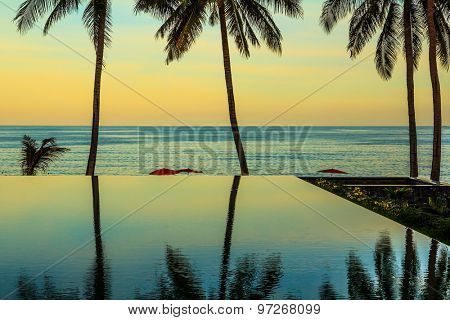 Delicate sunset on the popular resort island of Koh Samui. Palm trees reflected in smooth water of the pool on the beach