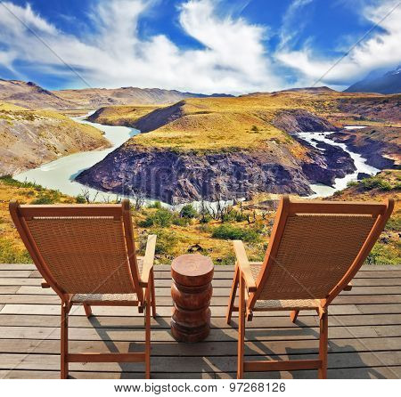 Two wooden chairs - on a wooden platform.  The comfortable place to enjoy the beauty of the landscape. The magnificent park Torres del Paine in Chile.  Picturesque river bends a horseshoe of hills.