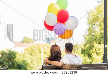 love, holidays, summer, dating and people concept - happy couple with air balloons in city sitting on bench