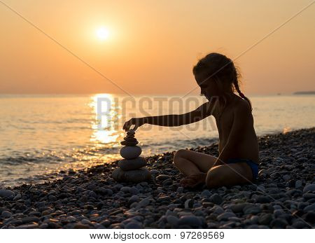 Silhouette Of Girl Builds Pyramid From Stones