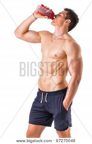 Muscular young man holding protein shake bottle
