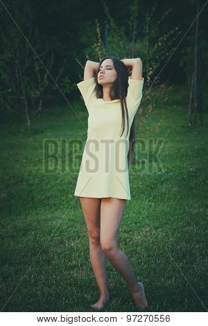 young barefoot woman wearing short retro dress stand barefoot on grass retro colors full body shot