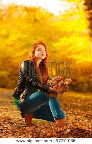 Girl Relaxing In Autumn Park Throwing Leaves Up In The Air.