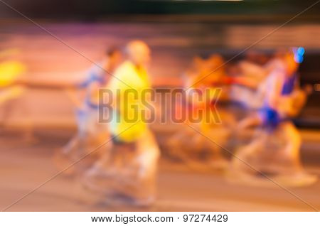 Blurred runner athlete running at night marathon. Man fitness silhouette evening jogging workout wel