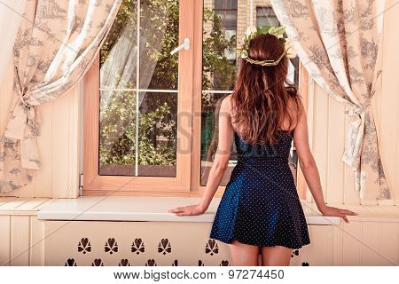 Girl Looking Out The Window. Girl Turned Her Back.girl In A Short Dress. On Beautiful Hair Is Wreath