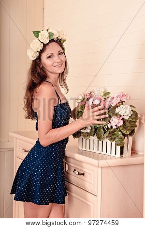 Girl Stands Near A White Dresser With A Wreath On Head. There Are Flowers On The Dresser.