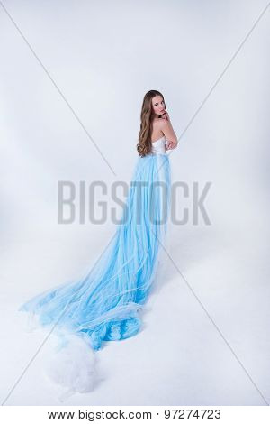 Beautiful Girl In A Blue Long Dress With Plume On A White Background