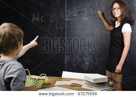 little cute boy in glasses with young real teacher, classroom studying