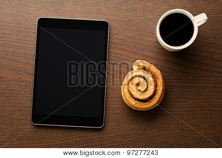 Cinnamon roll, cup of coffee and computer tablet. Business breakfast.