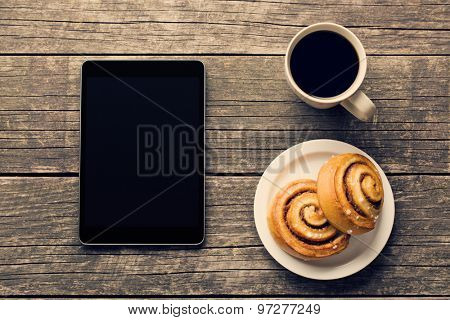 Cinnamon rolls, cup of coffee and computer tablet. Business breakfast.
