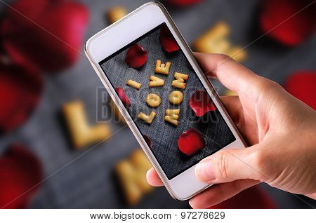using mobile phone to take photos of Cookies ABC in the form of word I LOVE MOM alphabet with red ro