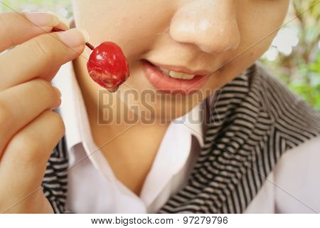 Woman Eating Red Cherry At Cake Shop.