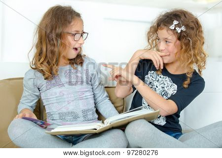 Two sisters reading a book