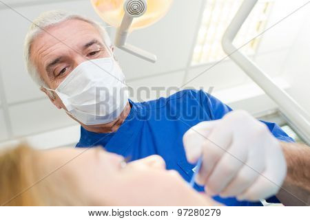 Dentist using a scraper