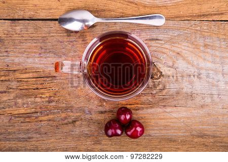Cup Of Tea, Spoon And Sweet Cherry On A Wooden Background