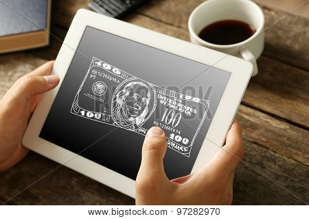 Money concept. Hands holding digital tablet with dollars image on it, close-up