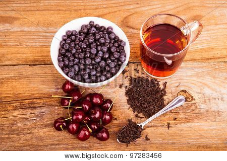 Cup Of Tea, Sweet Cherry And Blueberry In White Bowl On A Wooden Background