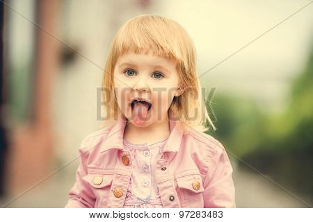 Beautiful 2 year old girl showing tongue  in the street close up