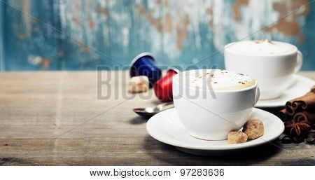 Two cups of cappuccino with coffee beans, spices and capsules on wooden background