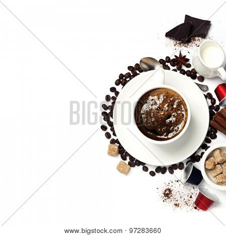 Top view of a cup of coffee with coffee beans, sugar, milk and capsules