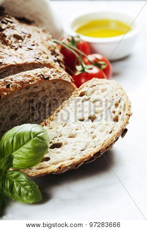 Tomato, bread, basil and olive oil on white marble background. Italian cooking, healthy food or vegetarian concept