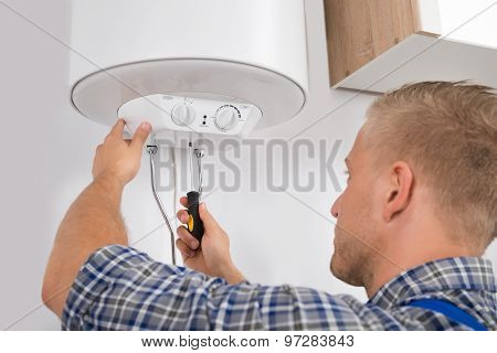 Worker Fixing Electric Boiler
