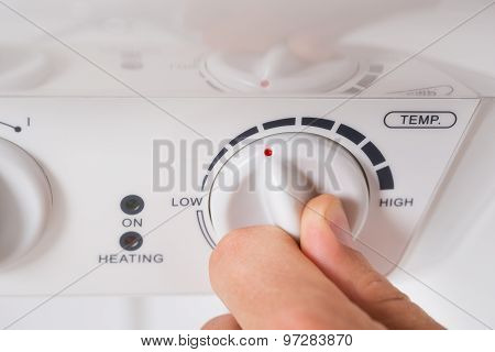 Person Turning The Knob Of Electric Boiler