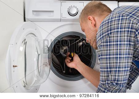 Worker Fixing Washing Machine