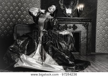 Black-and-white portrait of a beautiful renaissance woman in the lush expensive dress in an old palace interior. Vintage style. Fashion.