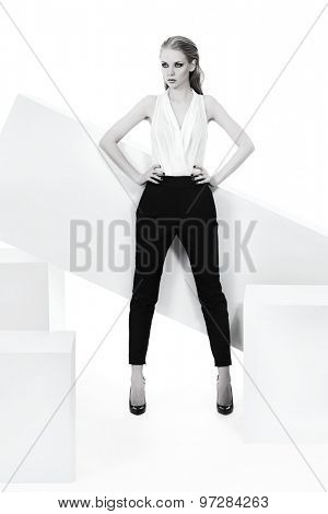 Fashionable female model posing at studio. Beauty, fashion photo. Clothing. Body care. Isolated over white. Black-and-white photo.