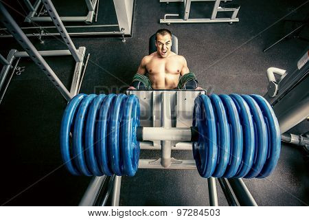 Muscular man weightlifter doing leg presses in gym. Sports.