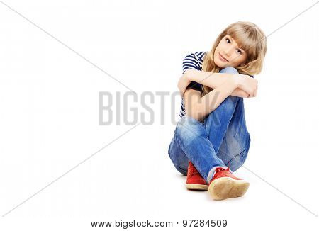 Full length portrait of a pretty teenager girl sitting on a floor. Isolated over white.