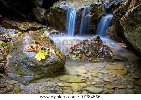 Small waterfall on mountain brook at autumn time