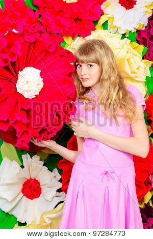 Pretty girl teenager posing in pink dress over bright floral background. Studio shot.