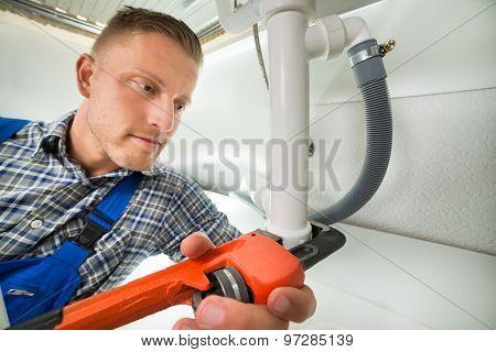 Plumber Repairing Sink Pipe