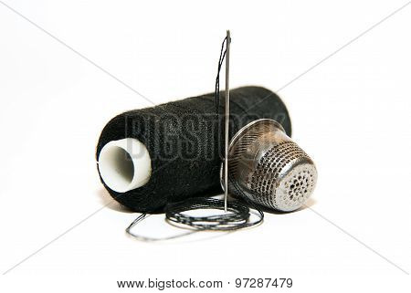 Needle, Thimble And Thread Spool On A White Background